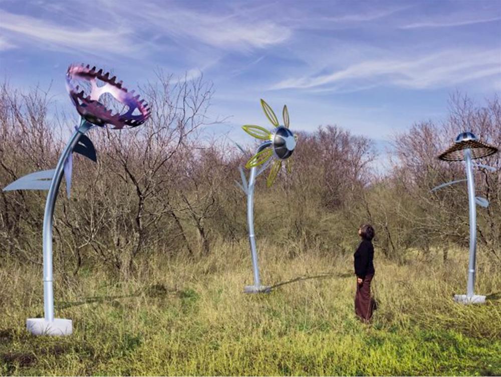 large metal flower sculptures in an field.