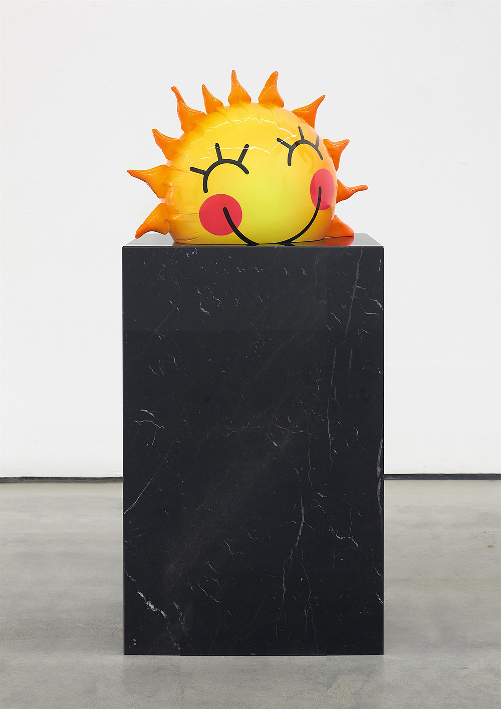 sculpture of a smiling sun on a pedestal
