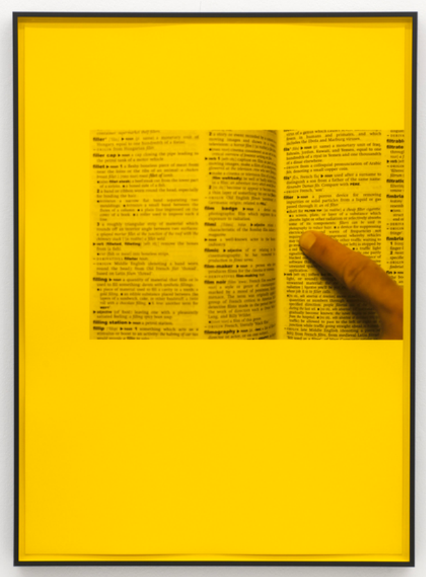 Yellow photographic print of dictionary and finger