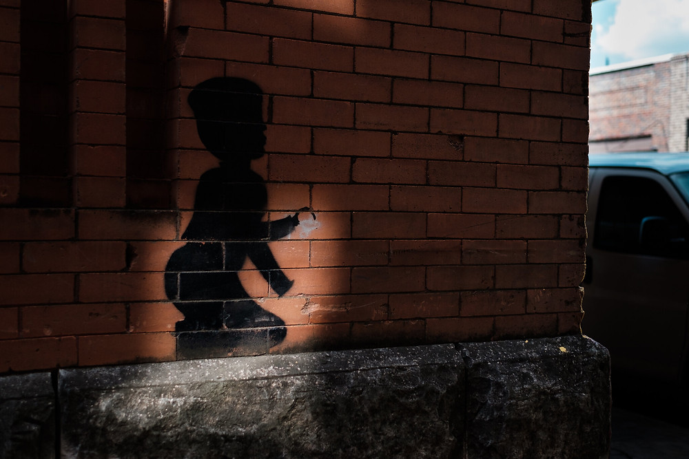 mural of a shadow child with a hook hand