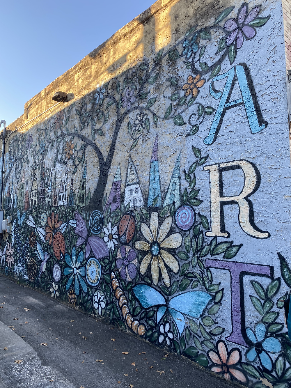 mural of flowers, homes and trees in downtown Athens TX