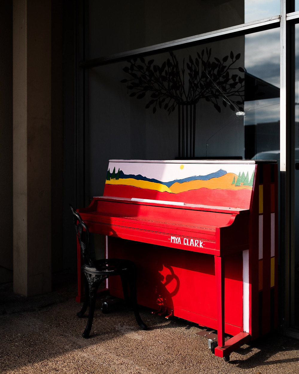 Red piano painted with trees and mountains