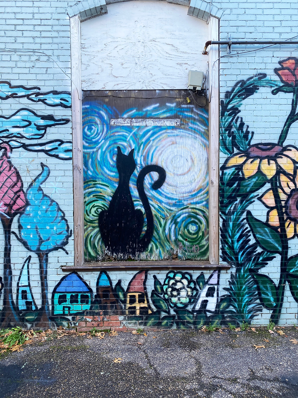 Painted mural of black cat, houses and flowers.