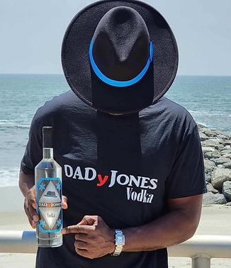 man wearing fedora hat holding DADyJones vodka bottle AT THE BEACH pointing to bottle