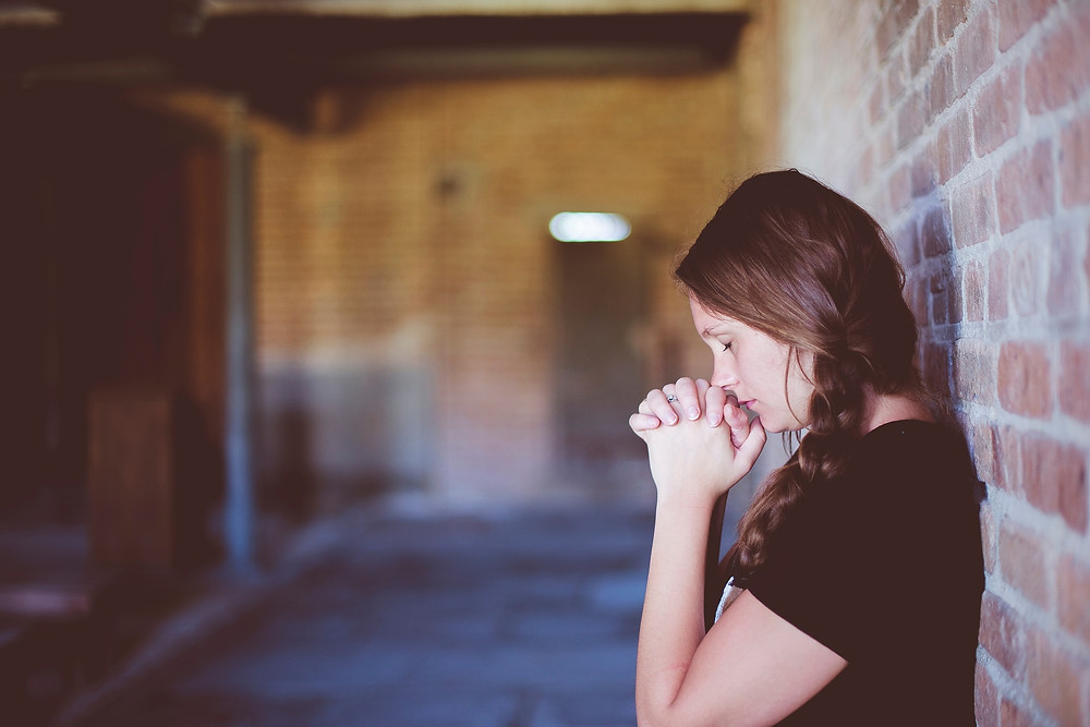 young woman eyes closed in prayer