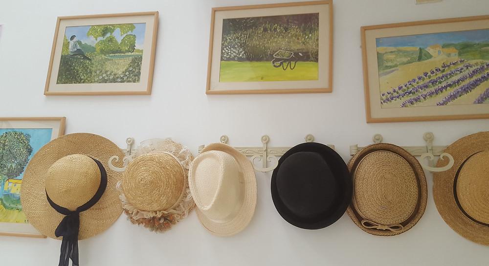 קיר מקושט בכובעים בכניסה לצימר