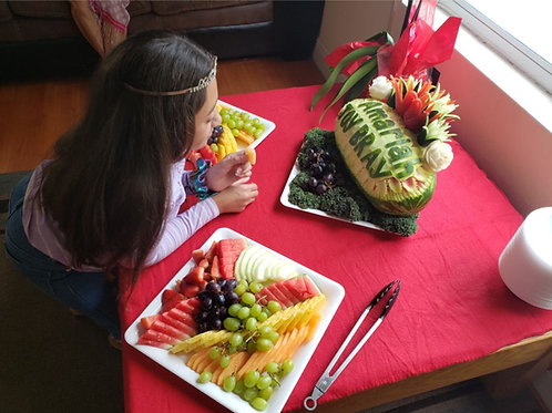 Large watermelon carving with two platters of assorted fruits