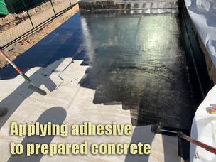 Applying adhesive to prepared concrete