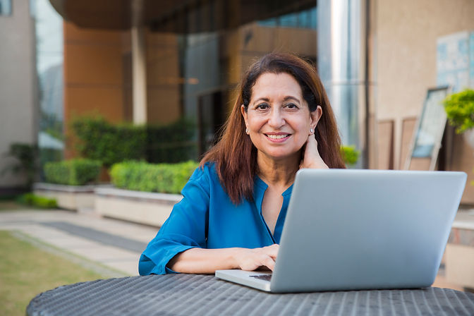 Woman sitting outside, working on a laptop computer