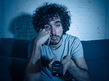 Young bored man on couch using TV remote