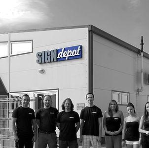 Signdepot csapattago a Signdepot Europe Kft. épülete előtt, fekete-fehérben
