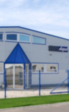 Signdepot Europe Kft. szürke-kék épülete, fókuszban a bejárattal és kerítéssel