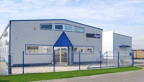 Signdepot Europe Kft. kék-szürke épülete fókuszban a bejárattal és kerítéssel