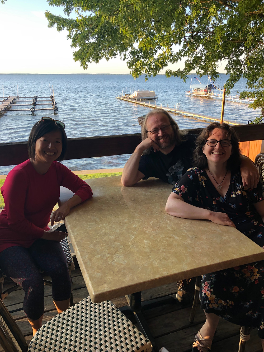 Y.S. Lee, Patrick Samphire, and Stephanie Burgis at a restaurant on a lake