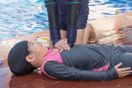Boy helping drowning child girl in swimm