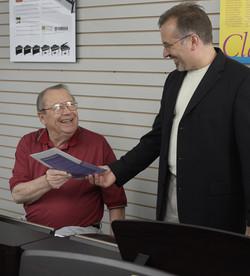 Happy Senior - Teacher handing music