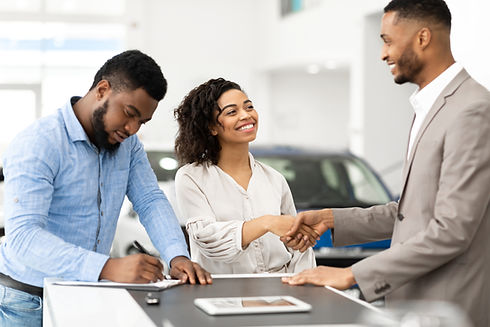 couple-shaking-hands-with-salesman-in-ca