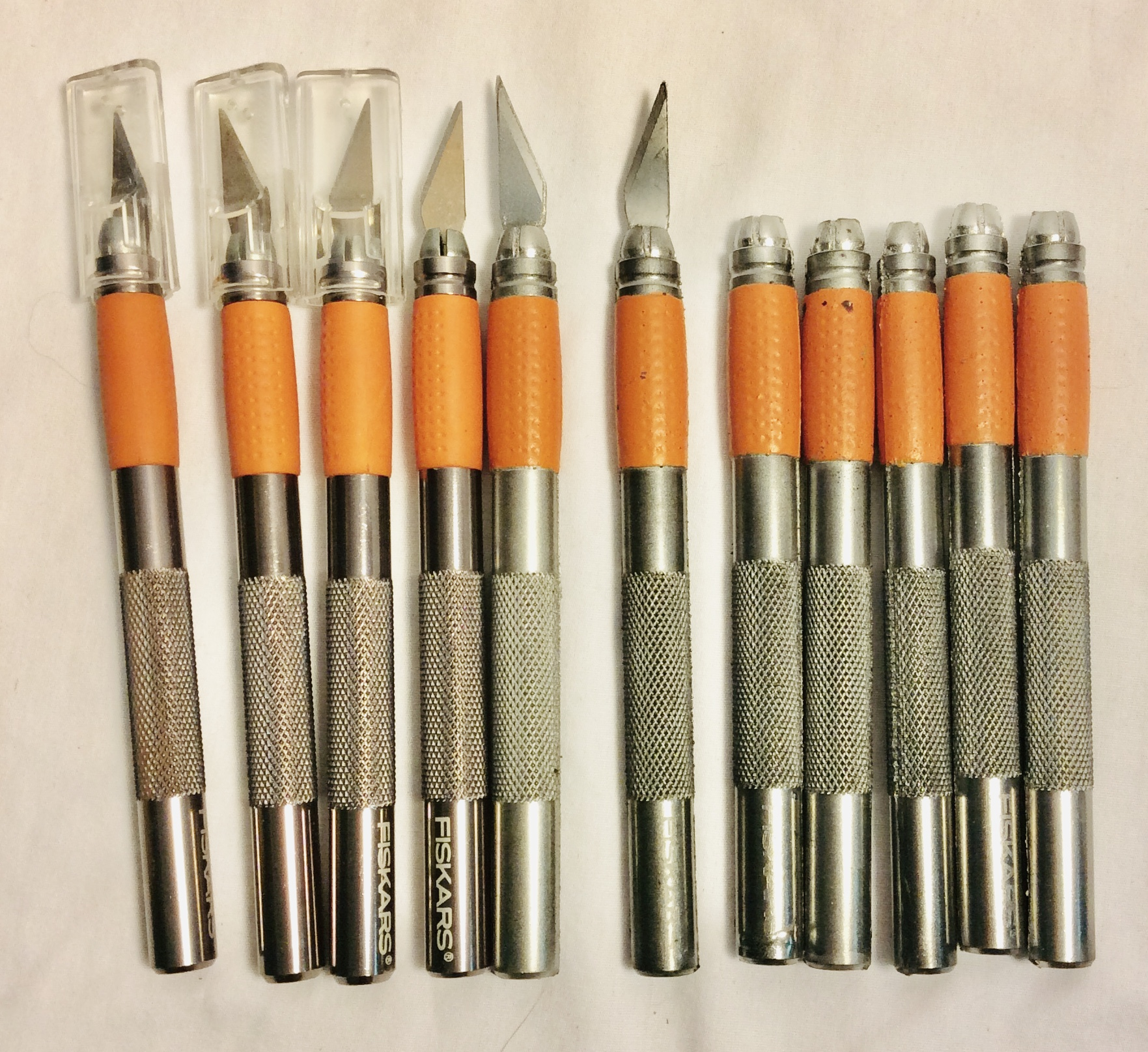 silver and orange x-acto knives (x7 rubber blades, x4 dulled, x2 boxes of sharp blades) x11
