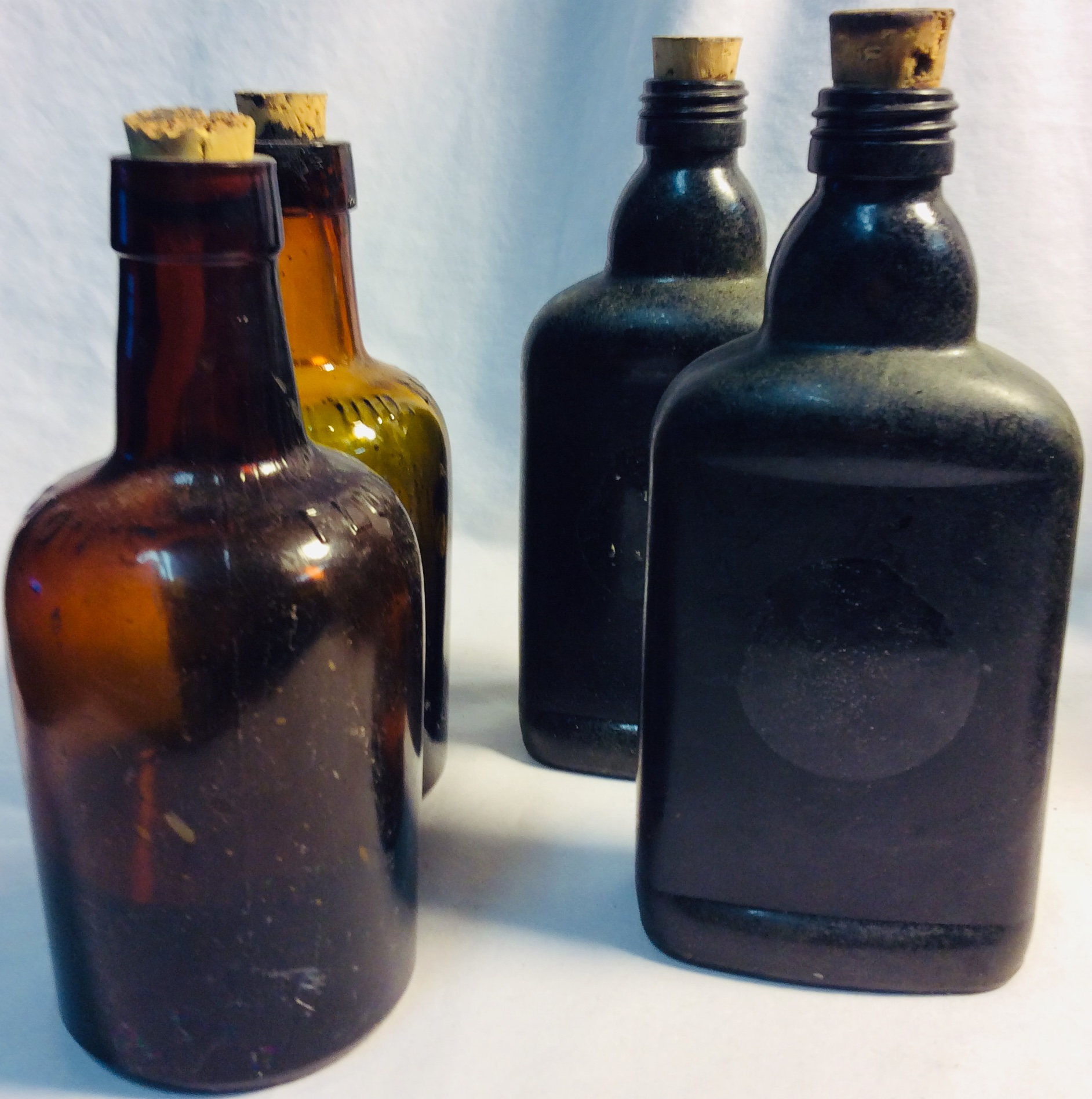 Antique brown glass bottles. x2 with dark liquid inside.