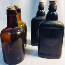 Antique brown glass bottles. x2 with dark liquid inside.