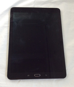Black tablet with a home button. Samsung logo on back