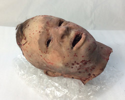 Decapitated rubber head with no eyes, blood splattered.