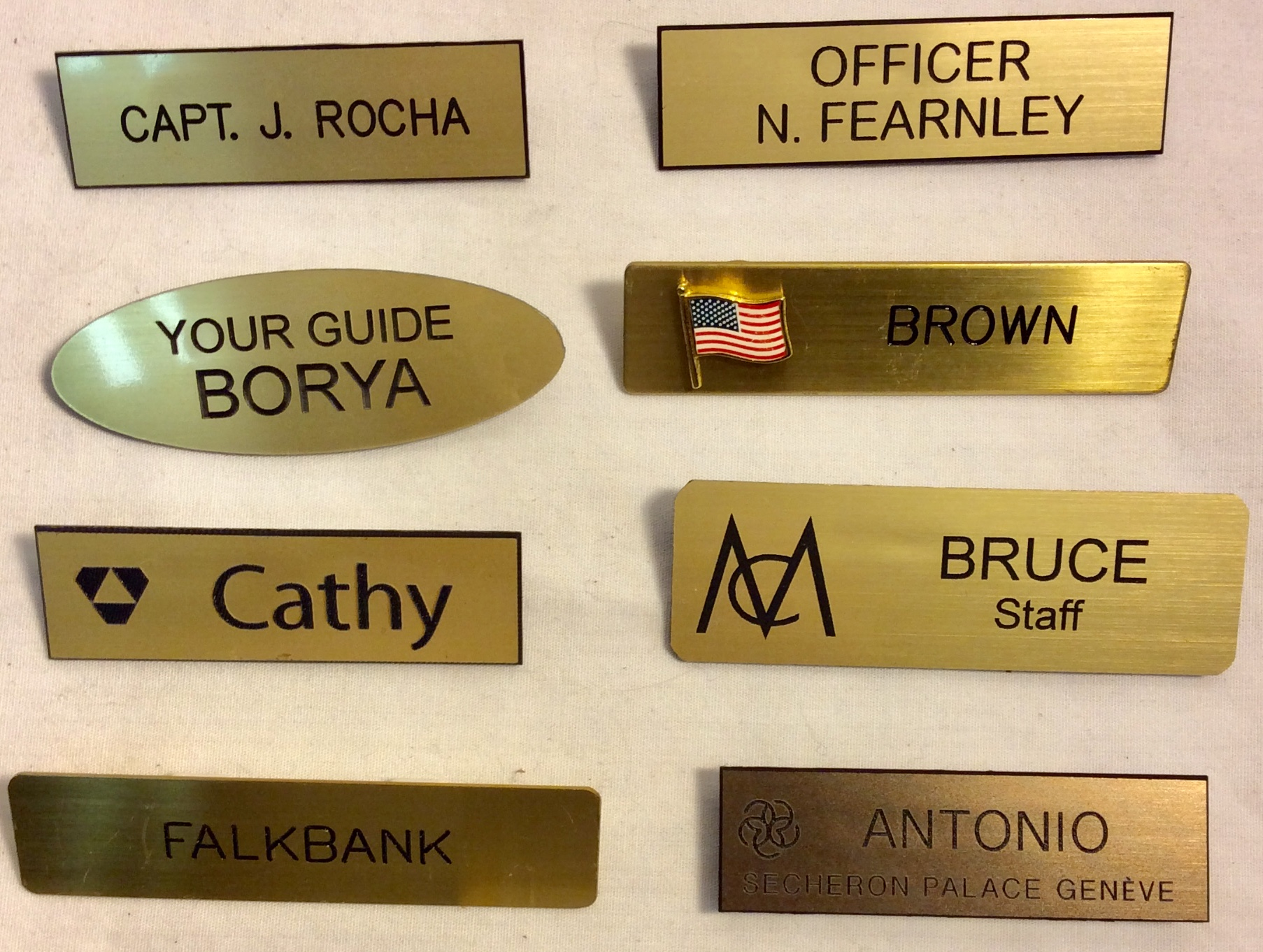Assorted name tags with black lettering on golden