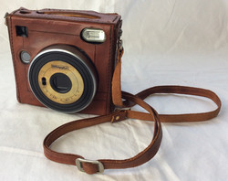 Vintage fictional brand polaroid with leather case and strap.