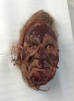 Decapitated rubber head with hair, covered in blood. Eyes open.