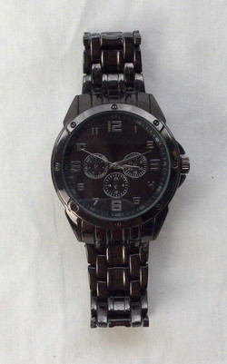 Bulky dark silver and black metal date watch.