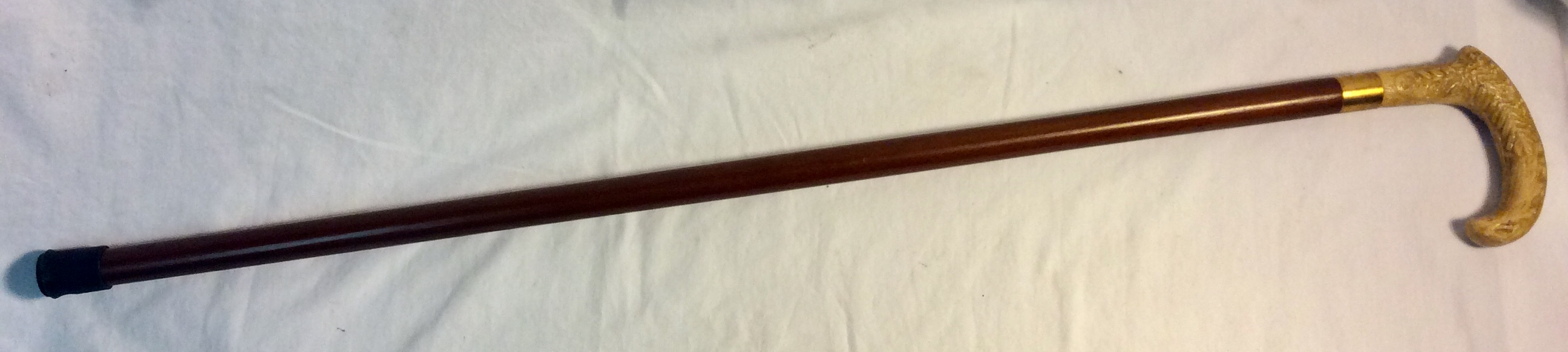 Brown wooden cane with carved faux