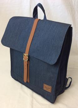 Blue denim herschel backpack with leather strap.