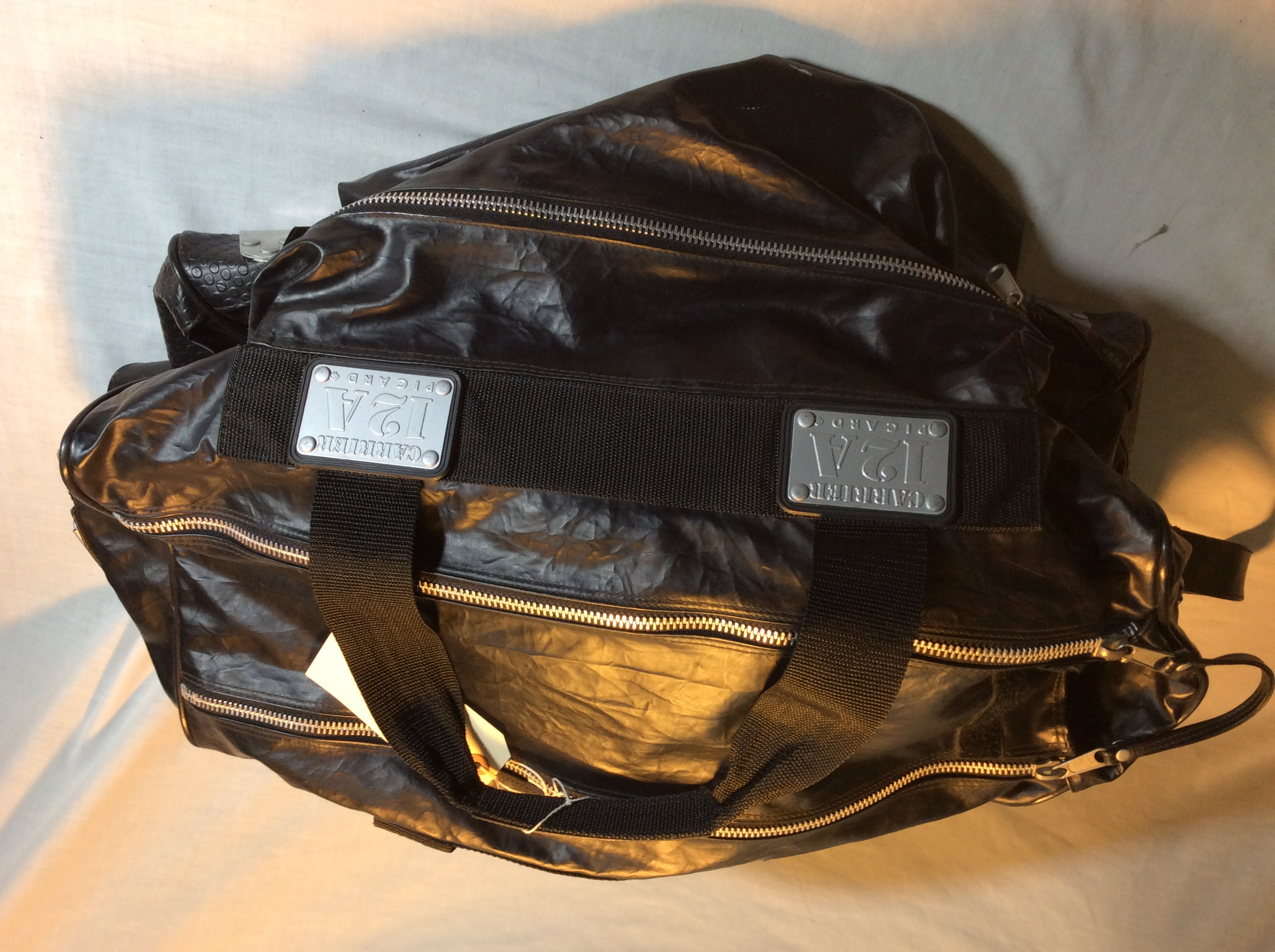 Black plastic/rubber duffel bag (Car