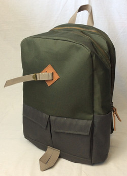 Green and grey vinyl backpack with strap detail.