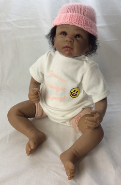 Realistic baby, can sit upright. Dark, curly hair.