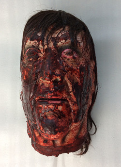Decapitated rubber head. Blood soaked. Eyes open and long hair.
