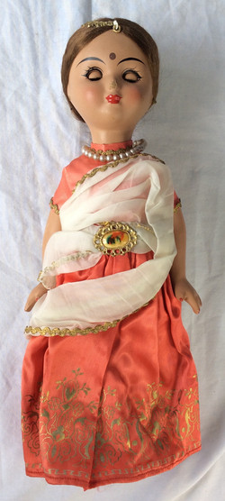 Vintage damaged doll with traditional outfit.