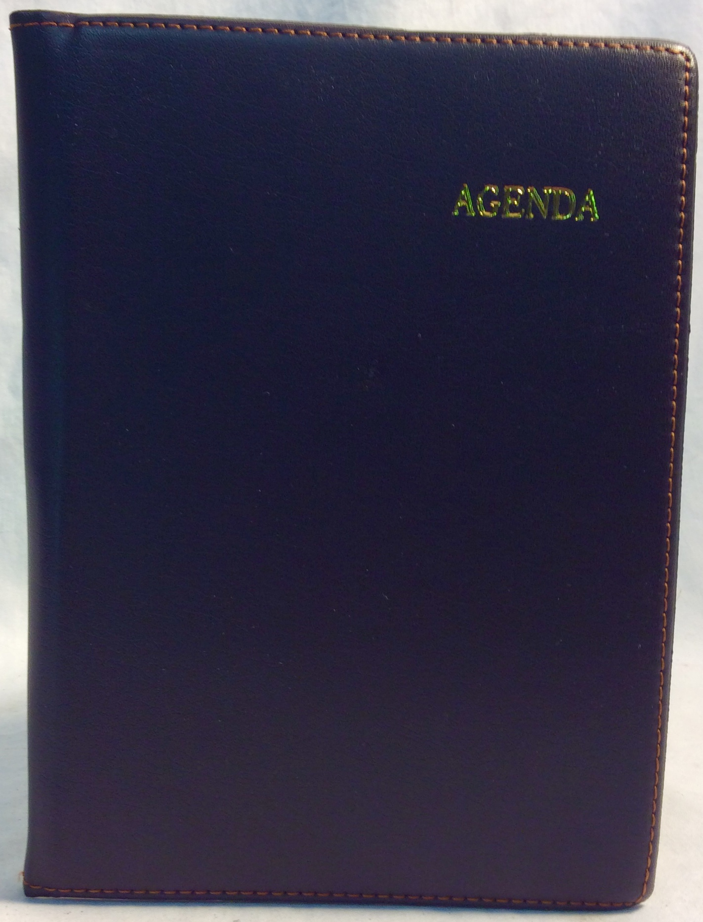 "Brown leather notepad cover with ""Agenda"" details in golden letters."