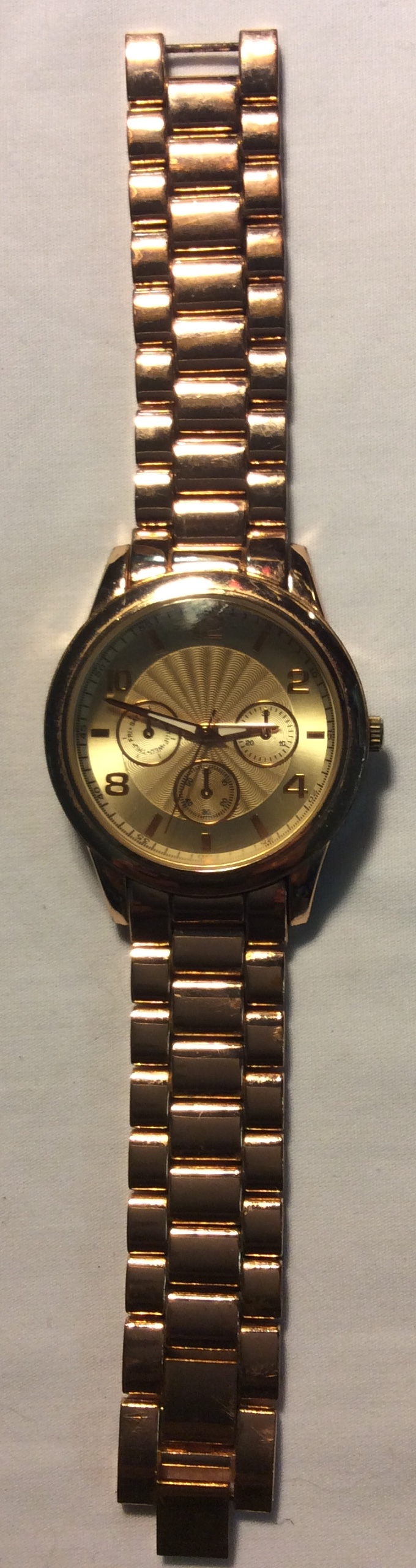 Round gold face with 3 smaller dials