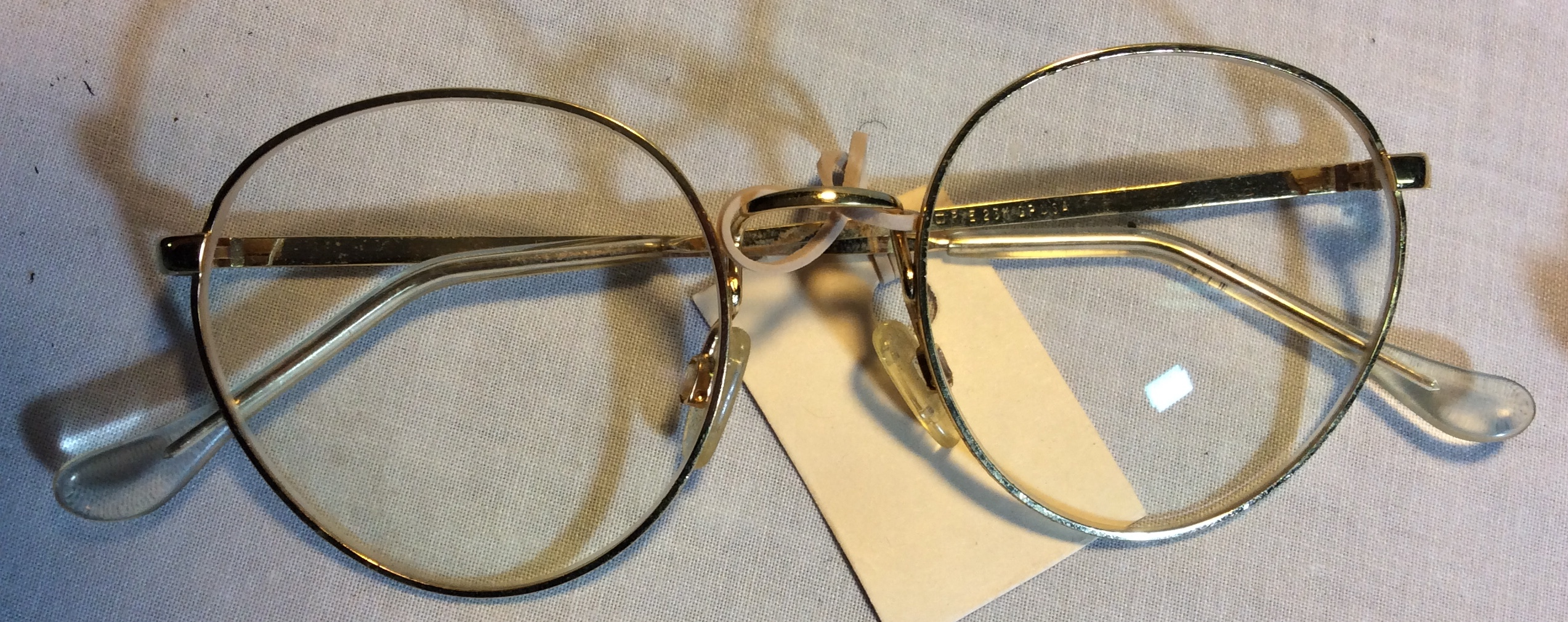 Large gold framed period eyeglasses