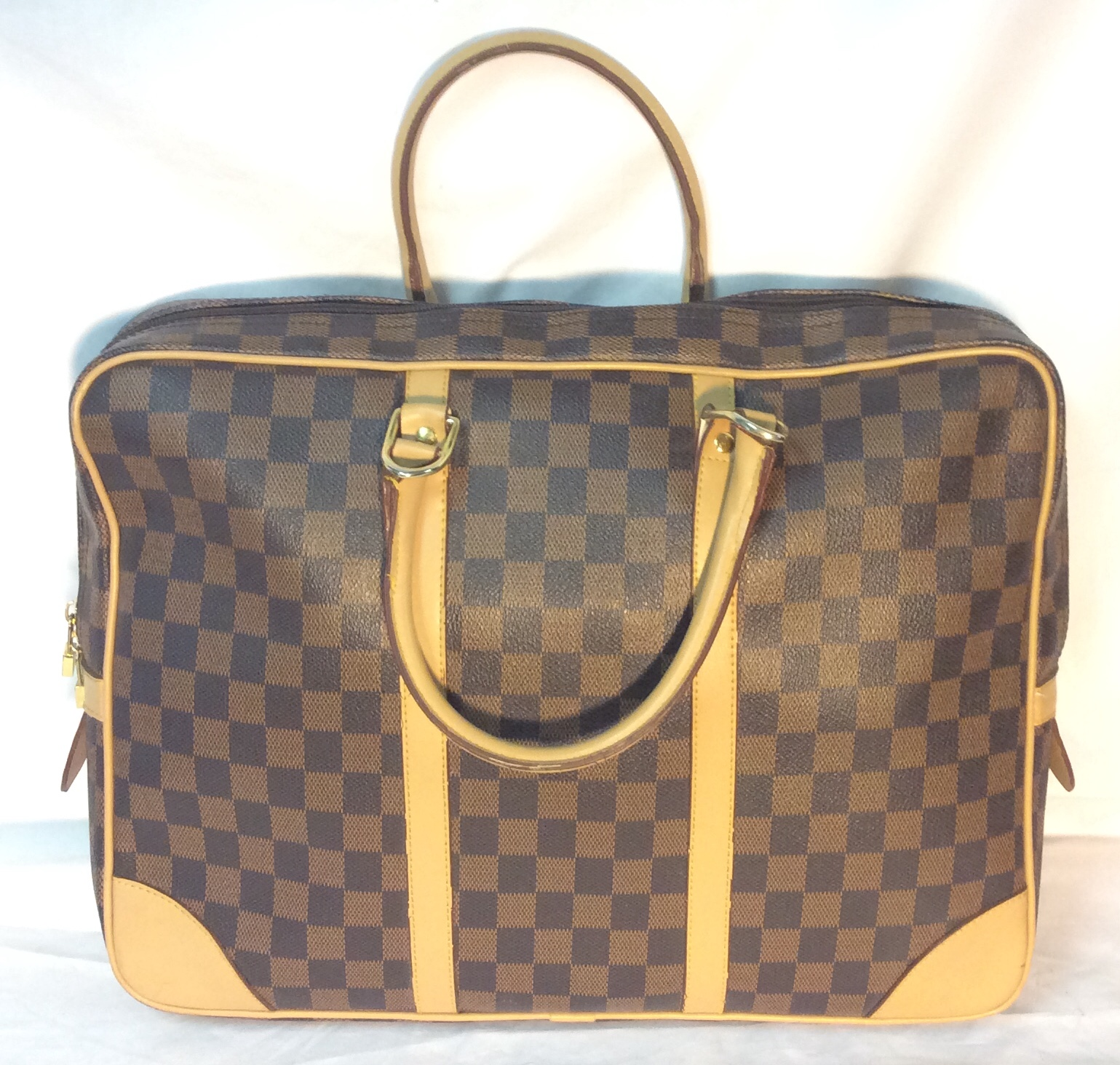 Brown checkered plastic travel bag