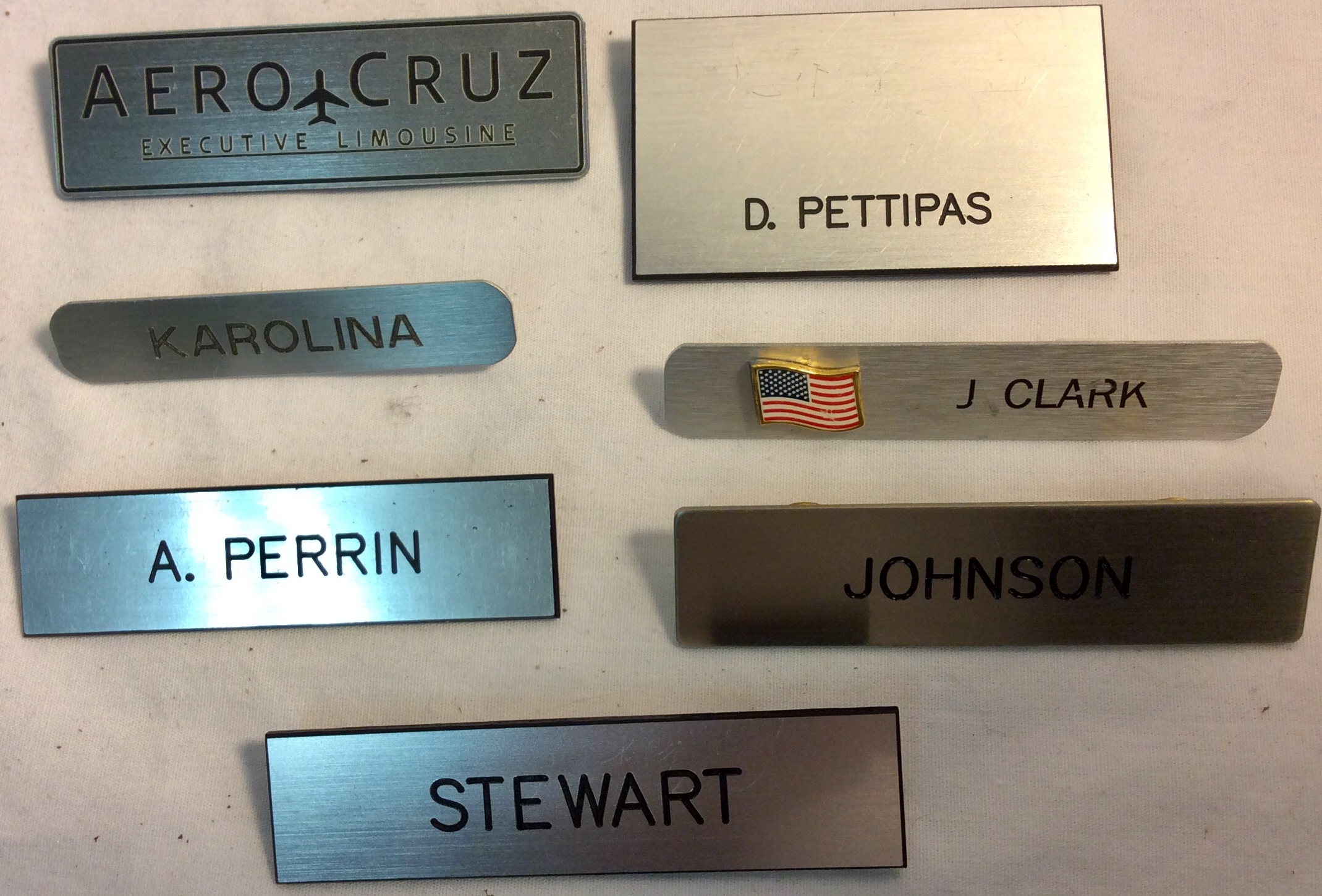Assorted name tags with black lettering on silver