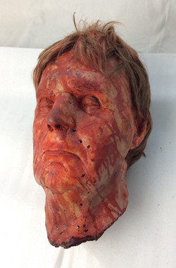 Decapitated rubber head. Blood covered, blonde hair, closed eyes. Older male.