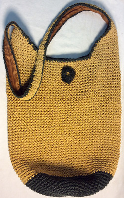 Togo woven wicker bag with black accents and flower on the front and fabric interior