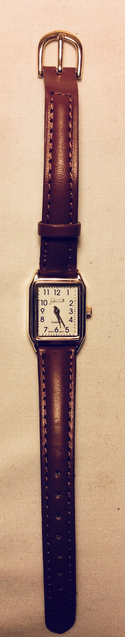 Gold framed white face watch