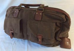 Brown vinyl duffle bag with brown leather handles.