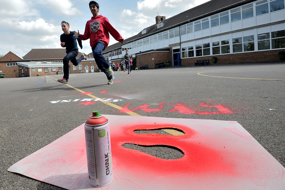 Students test out active landscapes with chalk spray in the playground