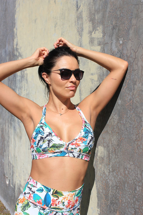 Model is wearing sunglasses and flowery print bra with matching pants.