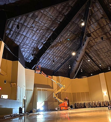 Dramatic interior of mega church with bucket lift installing lights in ceiling