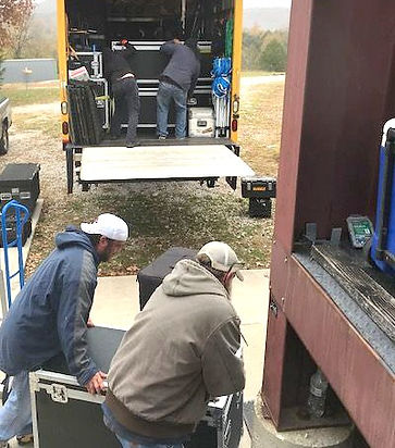 Crew members unloading stage equipment from truck onto back of outdoor stage
